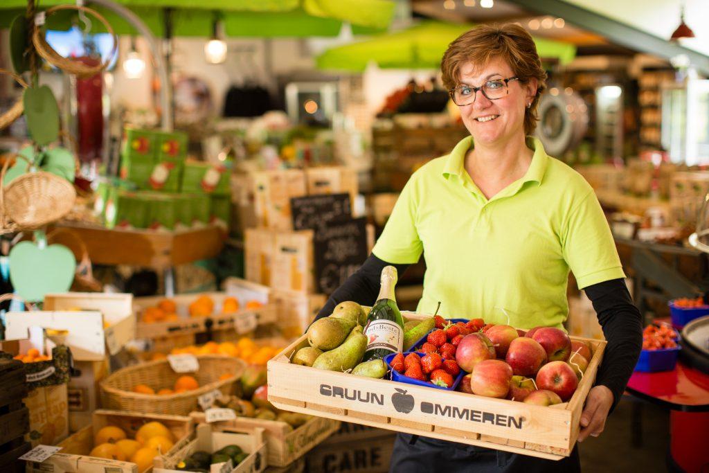 vrouw met kist met fruit in winkel Natuurlijk Gruun