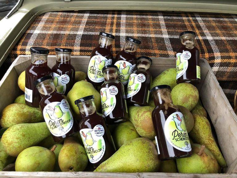 perenstroop in flesjes in houten kist tussen de peren