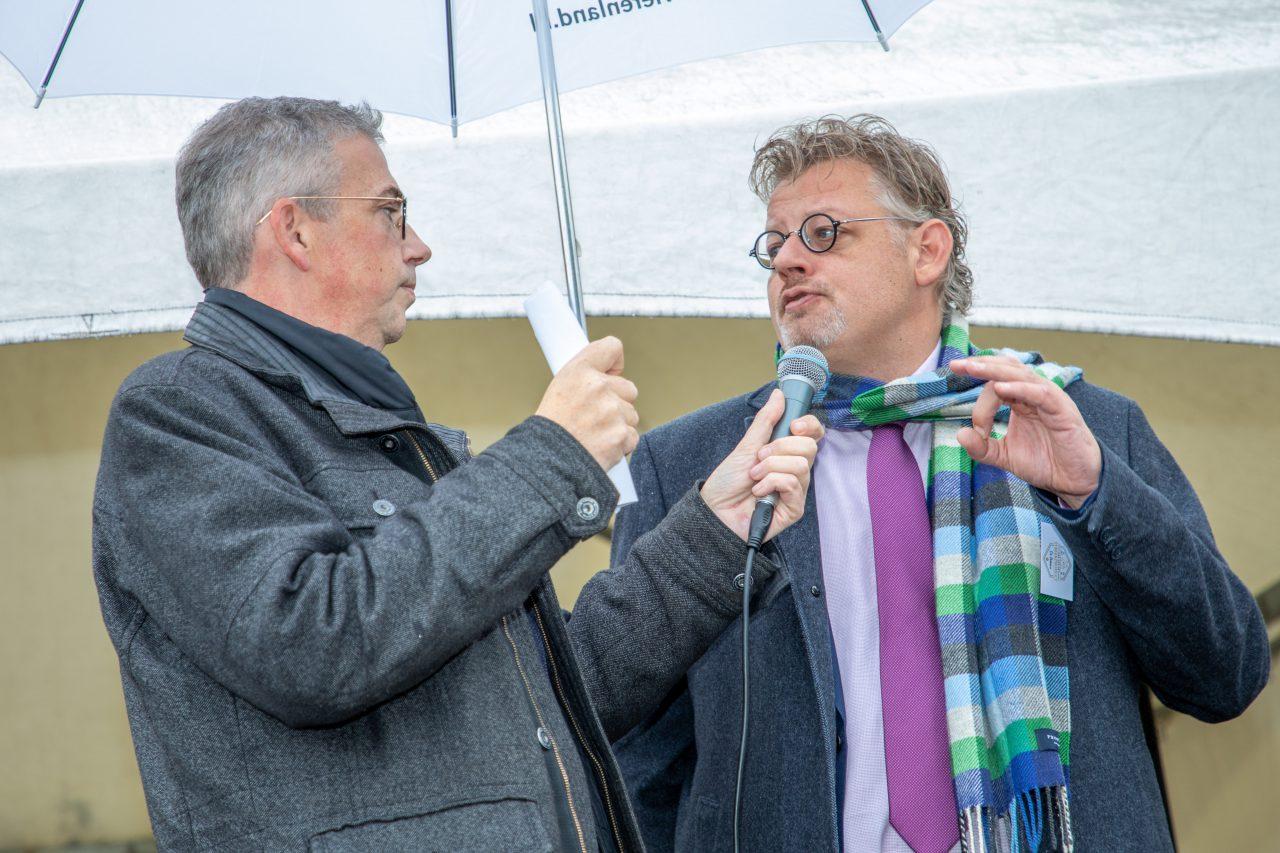 twee mannen met microfoon onder een paraplu
