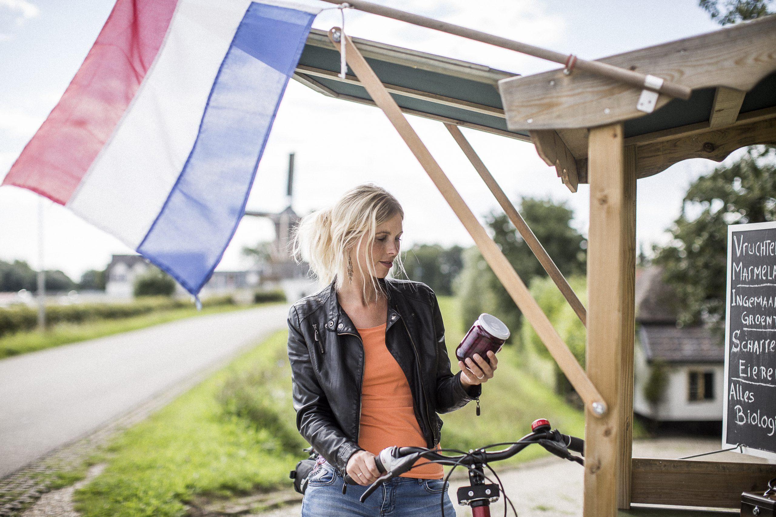 Vrouw met fiets bij kersenstal