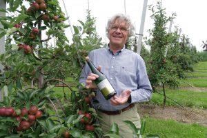 man met fles wijn in boomgaard bij natuurlijk gruun